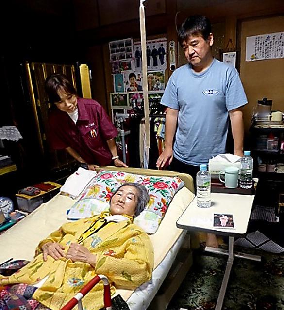 「元気が出るのは、みんなの助けがあるから」と話す母親(手前)を見守る郡山雅也さん(右)と担当のケアマネジャー=大阪市