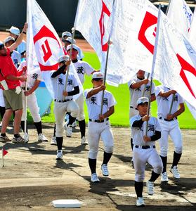 九州各県から贈られた寄せ書き入りの旗を手にリハーサルを行う野球部員たち=藤崎台県営野球場