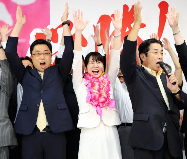 支持者らと万歳して当選を喜ぶ高瀬弘美氏(中央)。左は比例区で当選を決めた秋野公造氏=10日午後8時21分、福岡市東区、森下東樹撮影