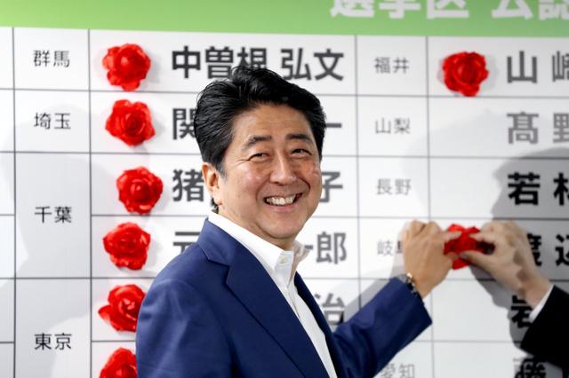 自民党の開票センターで当選確実となった候補者の名前に花をつける安倍晋三総裁=10日午後9時46分、東京・永田町、林敏行撮影