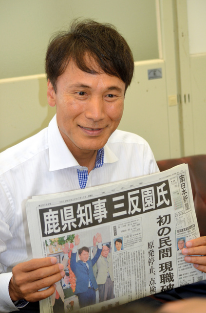 鹿児島県知事選での当選を報じる新聞を掲げる三反園訓氏=鹿児島市