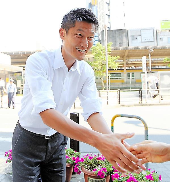 初当選から一夜明け、荻窪駅前で有権者らと握手する自民の朝日健太郎氏=11日、東京都杉並区、坂本進撮影