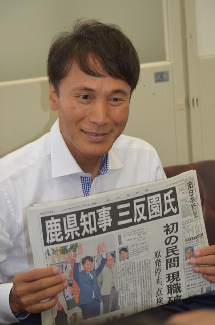 知事選での当選を報じる新聞を掲げる三反園訓氏=鹿児島市