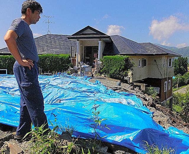 森尾寛昭さんが経営するペンション「ティンクナ」は、土台近くの斜面が崩れ建物がゆがんだ=6日、熊本県南阿蘇村