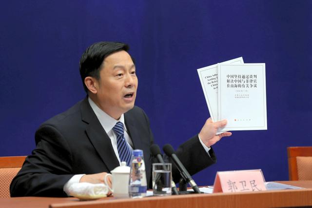 13日、北京での記者会見で「白書」を手に話す中国国務院新聞弁公室の郭衛民・副主任=ロイター