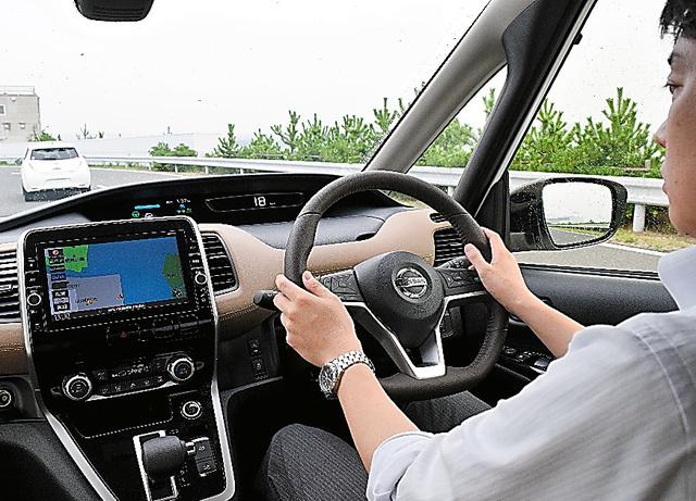 前の車について低速で自動的に走る日産自動車の「セレナ」。ハンドルを握っているが、操作は車が勝手にしてくれる=神奈川県横須賀市