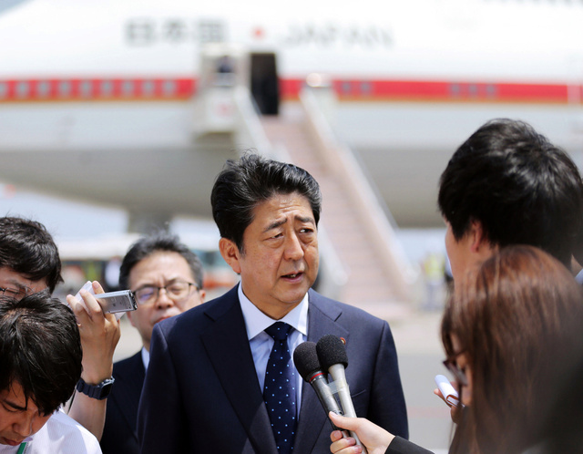 モンゴルへの出発前、記者の質問に答える安倍晋三首相=14日午前、羽田空港、時事