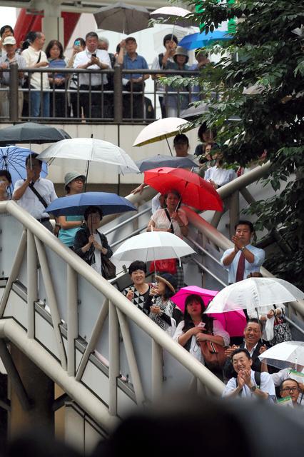 雨の中、JR立川駅前で候補者の演説に足を止める有権者ら=14日午後4時36分、東京都立川市、遠藤啓生撮影