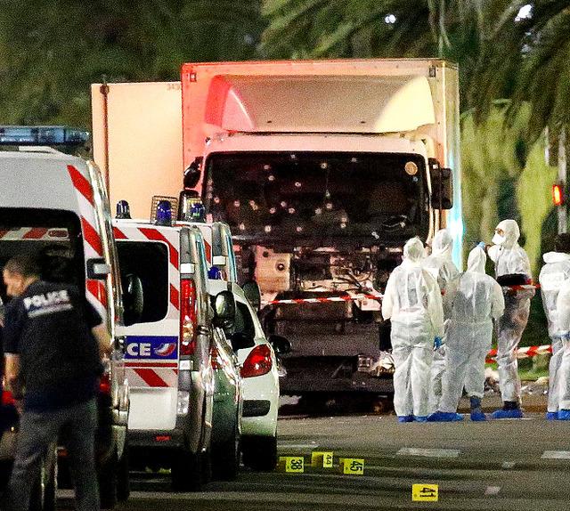 フランス南部ニースで、花火の見物客に突っ込んだトラック周辺に集まる警察官ら=ロイター