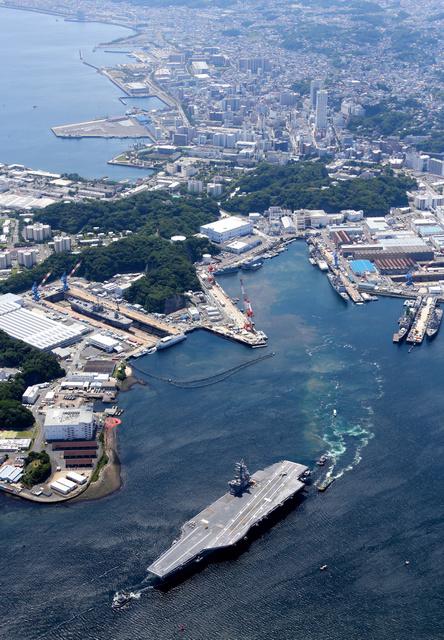 出港する米海軍の原子力空母ロナルド・レーガン。後方は横須賀市街地=6月4日午前、神奈川県横須賀市、朝日新聞社ヘリから、堀英治撮影