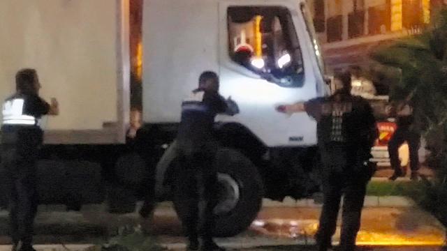 仏南部ニースで14日、事件を起こしたトラックの運転席にライトを当て取り囲む警官=AP