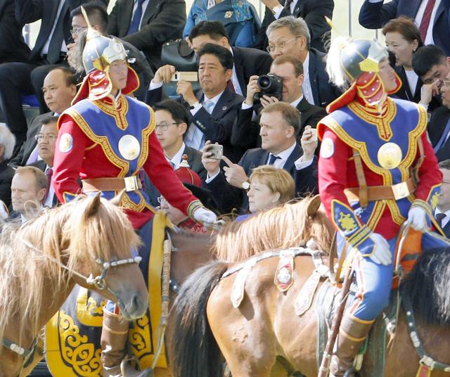 モンゴルの祭り「ナーダム」を観賞する安倍晋三首相。右隣はロシアのメドベージェフ首相=15日、ウランバートル、代表撮影