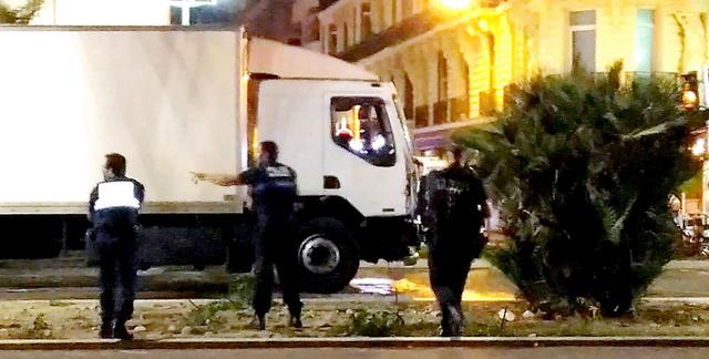 <暴走の末> 仏南部ニースで14日、暴走したトラックを取り囲む警官。ビデオ映像から=AP