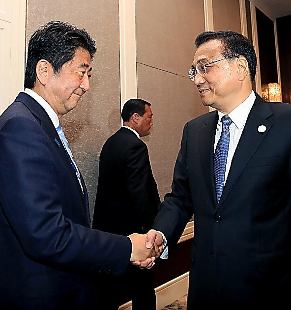 会談の前に握手を交わす安倍晋三首相(左)と中国の李克強首相=15日、ウランバートル、代表撮影