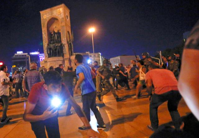 16日未明、トルコ・イスタンブール中心部のタクシム広場で、軍が空に向けて放った威嚇射撃で逃げ惑うエルドアン大統領の支持者たち=ロイター