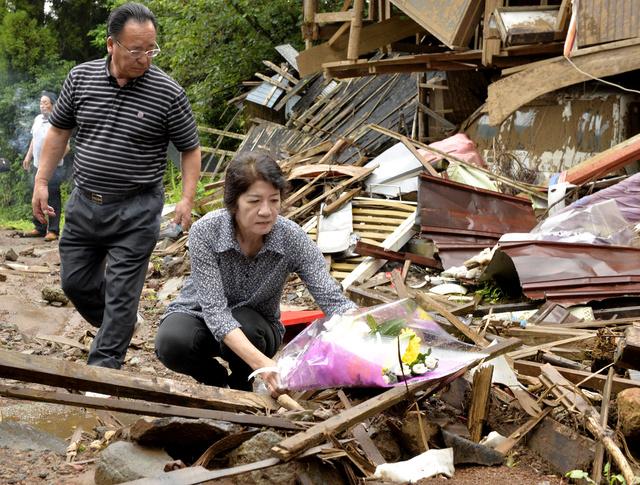 熊本地震の本震による土砂崩れで倒壊し住民が犠牲となった家に、近所の住民が訪れ花を捧げた=16日午前9時29分、熊本県南阿蘇村、福岡亜純撮影