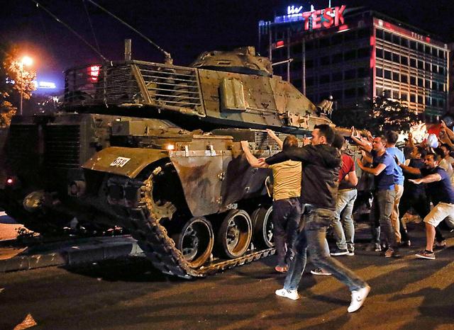 アンカラで16日、出動した軍の装甲車両を取り囲む人々=ロイター