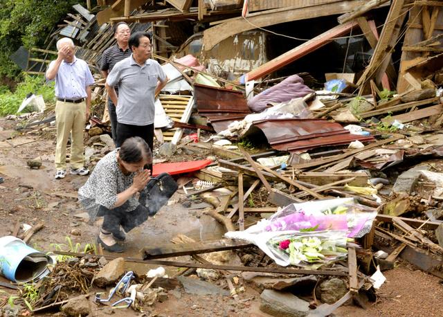 本震による土砂崩れで倒壊し住民が犠牲となった家に、近所の住民らが訪れ花を捧げた=16日午前9時31分、南阿蘇村、福岡亜純撮影