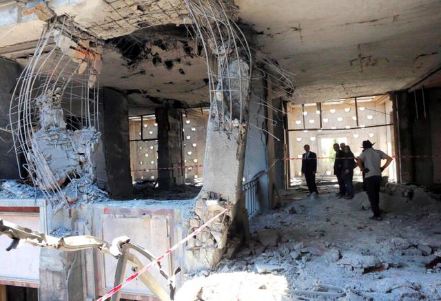 アンカラで16日、反乱軍によって空爆された国会の損傷を調べる人たち=AFP時事