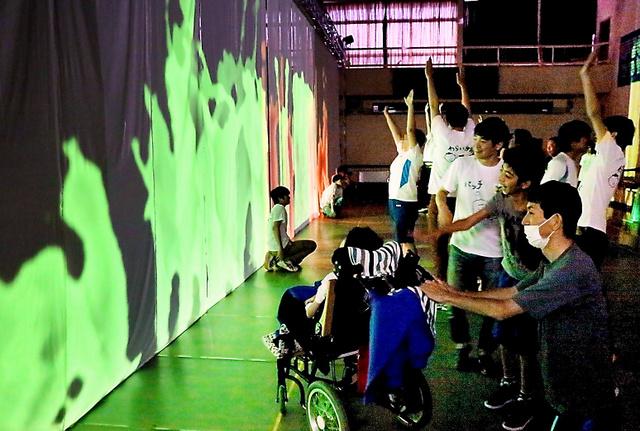 影メディア空間で遊ぶ県立石巻支援学校の子どもたち。緑色の二重残像影が幻想的だ=宮城県石巻市、三輪研究室提供(一部の生徒の顔にモザイクをかけています)