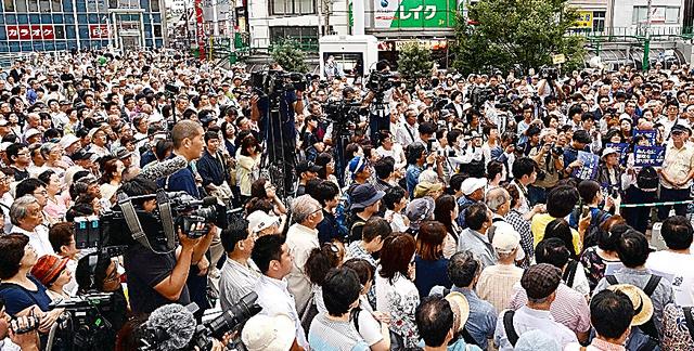 候補者の演説に耳を傾ける人たち=16日午後、東京都内