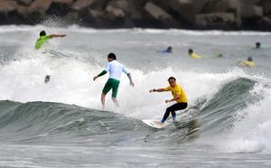 一斉に波に乗って競う大会参加者=17日午前、福島県南相馬市の北泉海岸、福留庸友撮影