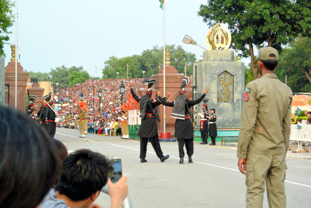 インド・パキスタン国境の国旗降納式で、インド側(奥)をパフォーマンスで挑発するパキスタンの国境警備隊員(中央)=ワガ国境、写真はいずれも武石英史郎撮影