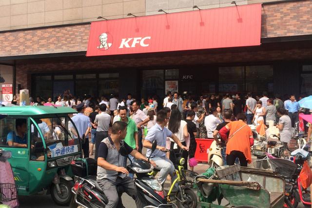 中国江蘇省宝応県で19日、ケンタッキーフライドチキンの店舗前に抗議のため集まった群衆を見守る人たち=AP
