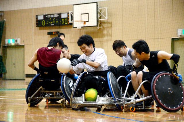 ボールを持つ堀貴志さんに守備をするチームメートが次々と車いすで激突した=17日、福岡市南区