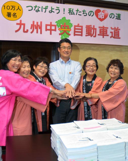 集まった約10万人分の署名を前に河野知事(中央)と握手をする女性団体の会長ら=県庁
