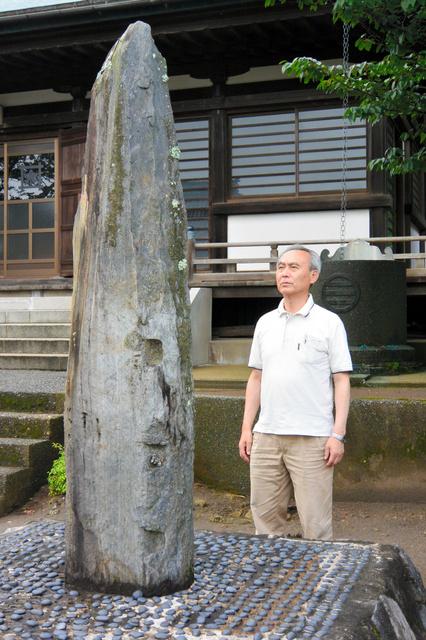 江戸時代の浜のにぎわいを伝える「繫船柱碑」と岩瀬洋男さん=千葉県勝浦市興津の妙覚寺