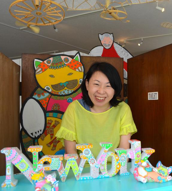 会場につくった「銭湯の番台」に座る松本倫子さん。天井には夫の秋則さんのオブジェを展示=平塚市明石町