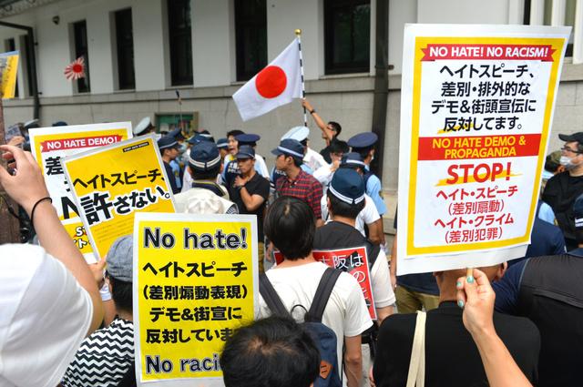 繁華街で街頭宣伝するグループに対し、ヘイトスピーチに反対する人たちも抗議に訪れた=17日午後、大阪市中央区