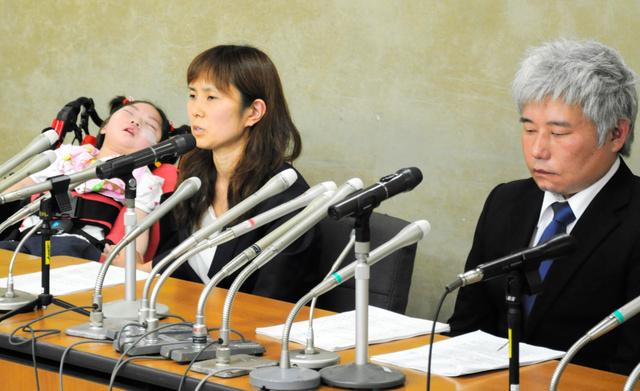 高橋心音ちゃん(左)とともに会見をする母の亜希子さん(中央)と父の歩さん=東京・霞が関の厚生労働省