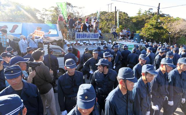 機動隊に囲まれながら移設予定地への進入口近くで抗議する建設反対派たち=22日午前7時36分、沖縄県東村高江、上田幸一撮影