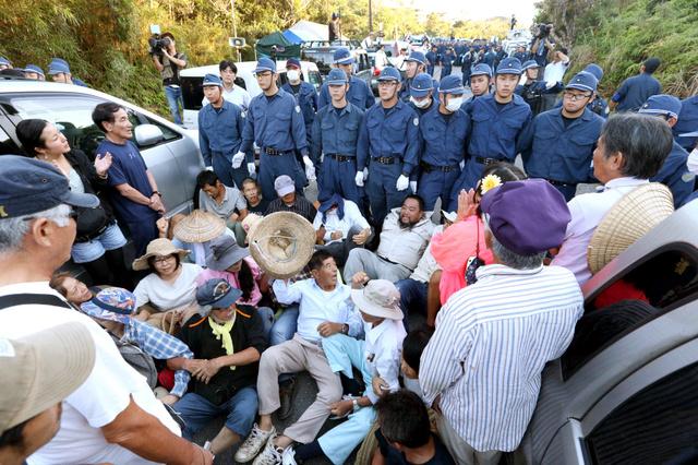 ヘリパッドの建設予定地に通じる進入口沿いの県道70号で、座り込みをして抗議する反対派の住民たち=22日午前6時32分、沖縄県東村高江、上田幸一撮影