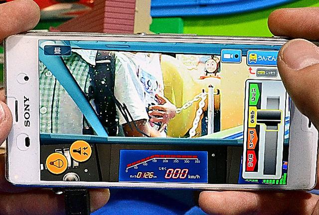 プラレールを操作するスマートフォンの画面には、車両に内蔵されたカメラの映像が映し出された=東京都江東区、工藤隆治撮影