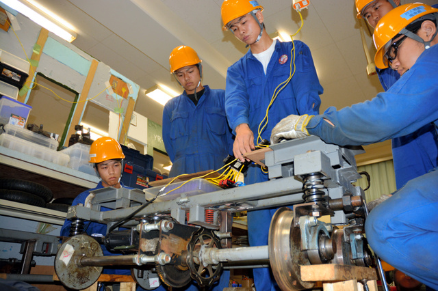 「キャパシター」と呼ばれる蓄電装置(中央の容器内)を電源に、手作りの台車を動かす川越工業高校の生徒たち=川越市西小仙波町