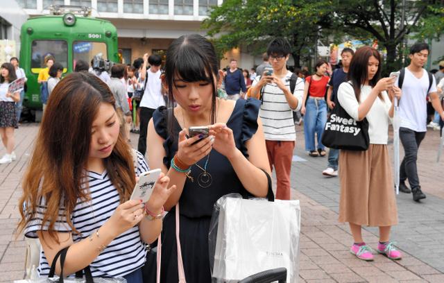 配信がはじまり、さっそく街中でポケモンGOを楽しむ人たち=22日午後2時19分、東京都渋谷区、諫山卓弥撮影