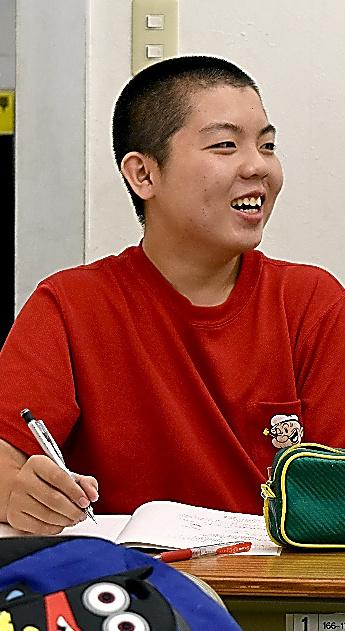 塾で笑顔を浮かべる安田翼樹さん。御船町の自宅周辺でも家屋は激しく壊れた=益城町