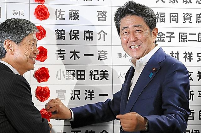 自民党の開票センターで当選確実となった候補者の名前に花をつける安倍晋三総裁(右)。左は高村正彦副総裁