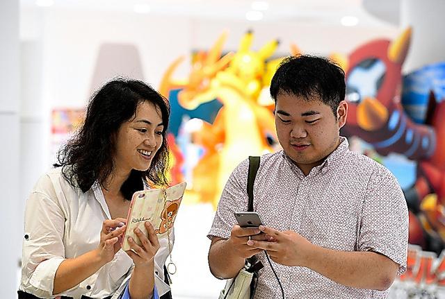 ポケモンGOの配信が始まり、ダウンロードして楽しむ人たち=22日午前11時31分、東京都豊島区、諫山卓弥撮影