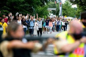 ミュンヘンで22日、銃乱射事件の現場付近のショッピングセンターから避難する人々=AFP時事