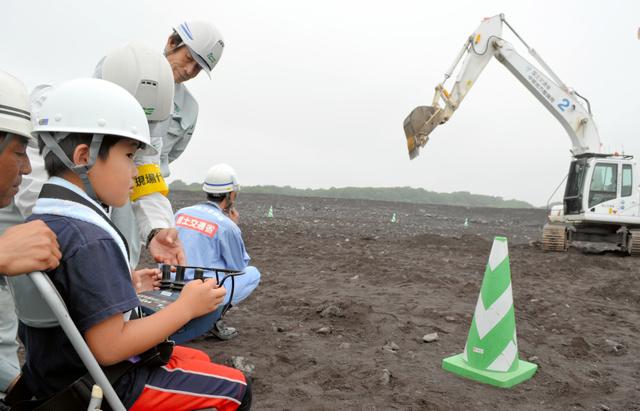 無人重機をリモコンで動かす小学生=富士宮市上井出