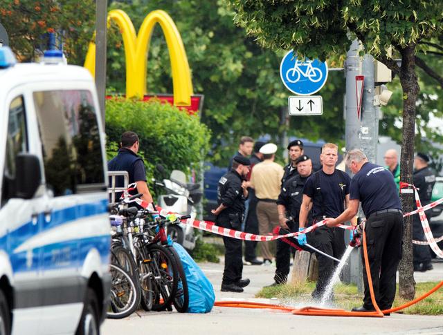 ドイツ南部ミュンヘンで23日、銃乱射事件があったマクドナルド前の犯行現場に立つ警察官=AP