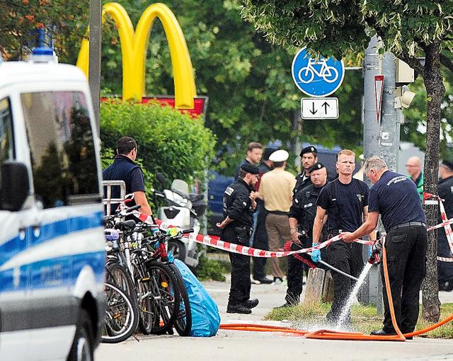 23日、銃乱射事件があったマクドナルド前の現場に立つ警察官=AP