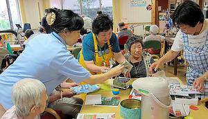 デイサービスで利用者と一緒に作業する「介護予防サポーター」(中央エプロン姿)=埼玉県和光市