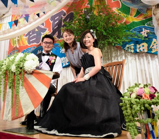 デニムドレス姿の(右から)豊島栄美さん、デザイナー柳谷理花さん、千葉尚之さん。後ろの大漁旗が石巻らしさを演出する=石巻市千石町
