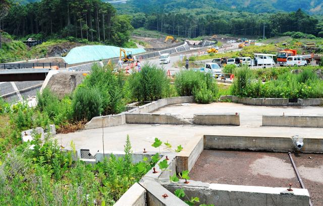 土石流にのみ込まれ、基礎部分だけが残った住宅跡(手前)。土石流が発生した大金沢(奥)では、新たな被害を防ぐ導流堤の建設が進む=12日、東京都大島町元町
