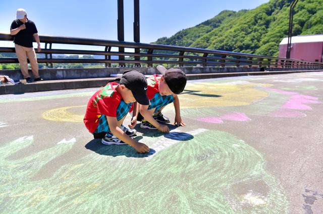 浅瀬石川ダムの天端に恐竜の絵を描く子どもたち=黒石市
